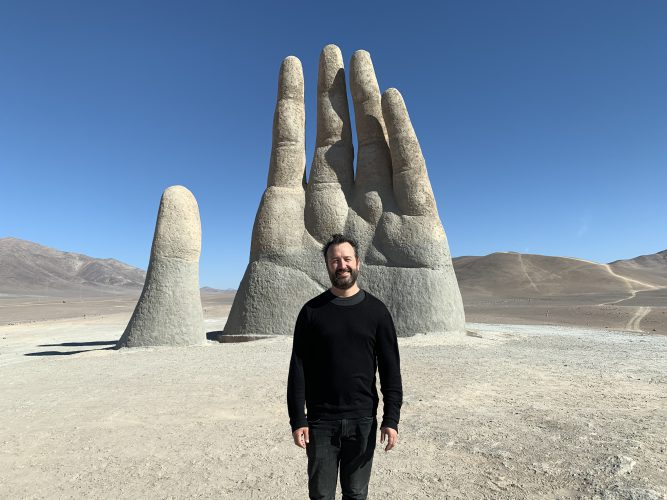 Man standing in front of a statue of a hand coming out of the ground that is twice as tall as he is